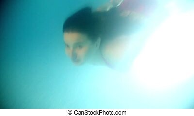 Brunette woman floating underwater