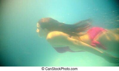 Brunette woman floating underwater