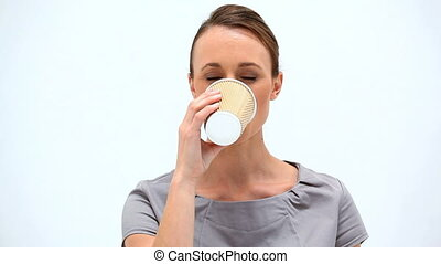 Brunette woman holding a cup of coffee against a white...