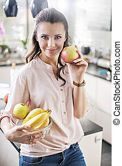 Brunette woman holding a fruit bowl