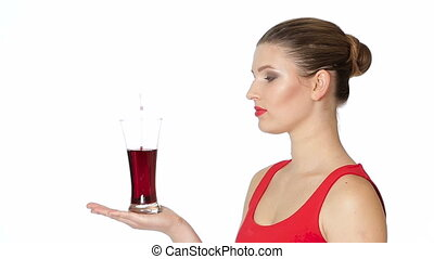 brunette woman holding a glass of cherry juice