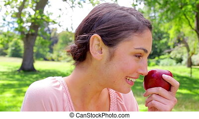 Brunette woman holding a red apple