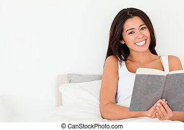 brunette woman holding book lying in bed looking into camera