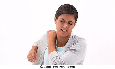 Brunette woman holding her painful shoulder against a white...