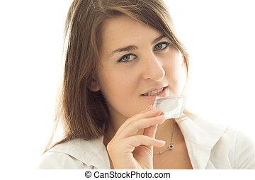 brunette woman holding packed condom against white...