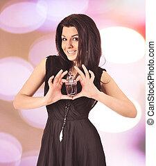 Brunette woman holding  perfume bottle.