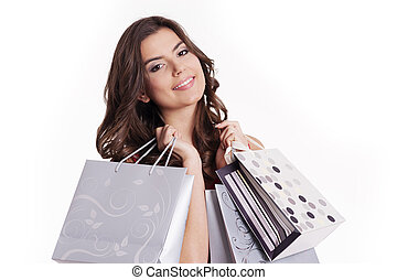 Brunette woman holding shopping bags next to her face