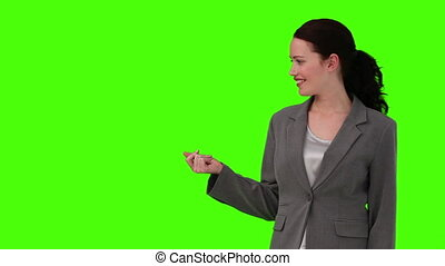 Brunette woman in a gray suit looking at the camera against a green screen
