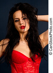 brunette woman in beautiful red lingerie on dark background