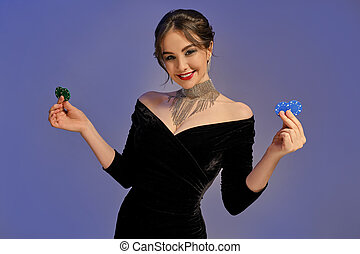 Brunette woman in black dress and shiny jewelry. Smiling, showing two blue and green chips, posing on purple background. Poker, casino. Close-up