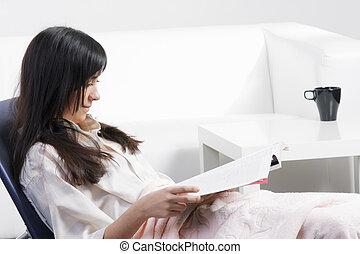 Brunette woman in chair reading