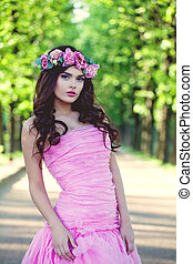 Brunette woman in flowers crown and pink dress outdoor