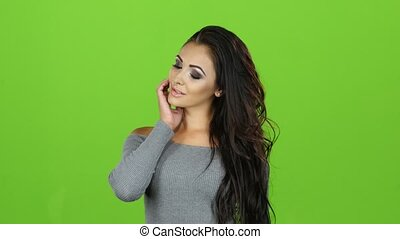 Brunette woman in gray sweater seduces and entices, green screen