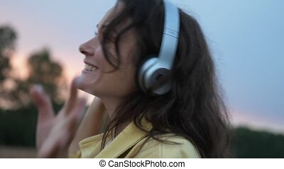 Young woman in headphones dancing in wheat field in summer time