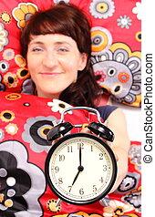 Brunette woman in her bedroom with alarm clock