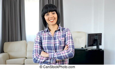 Brunette woman in her living room looking at camera and smiling