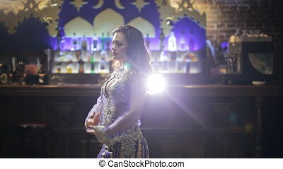 Brunette woman in lilac costume dances belly dance in front of bar.