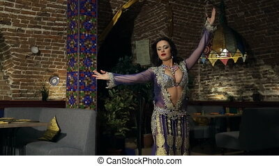 Brunette woman in lilac costume dances belly dance in restaurant.