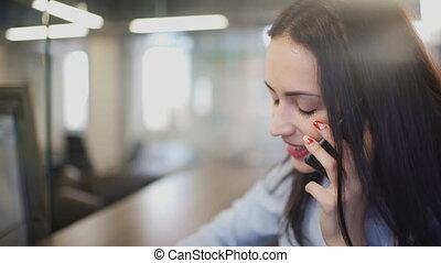 Brunette woman in office talking on telephone during break...