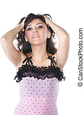 Brunette woman in pink touching hair