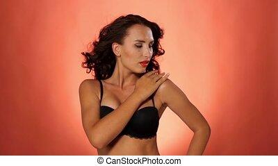 Brunette woman in sexual black bra on vinous background, slow motion