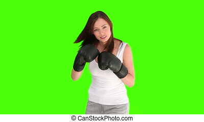 Brunette woman in sportswear holding box gloves