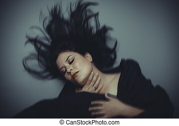 Brunette woman in studio shot with wind on hair .