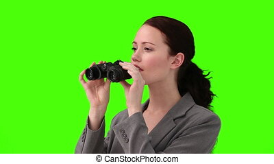 Brunette woman in suit looking for someone with a pair of binoculars