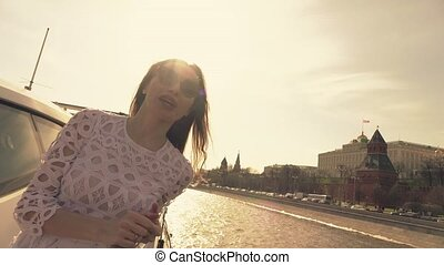 Brunette woman in sunglasses looks at Moscow Kremlin. Travel to Russia concept. Slow motion video