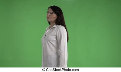 Brunette woman in white shirt posing against a green screen