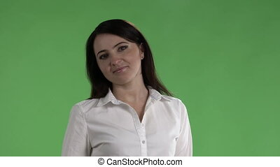 Brunette woman in white shirt standing against a green screen