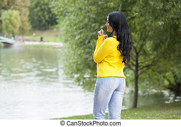 Brunette woman in yellow sweater on autumn street background
