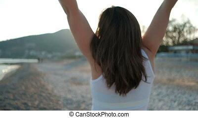 Brunette woman is glad to view sunlight on the coast of sea in holiday.