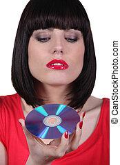 brunette woman looking a cd