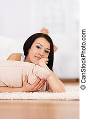 Brunette woman lying down on the carpet