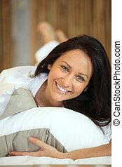 brunette woman lying on bed
