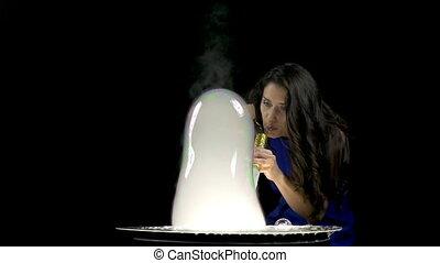 Brunette woman making large soap bubbles