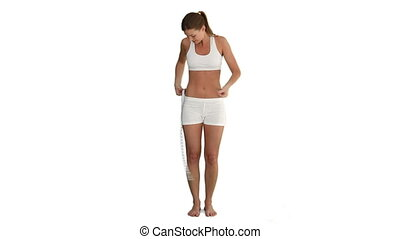 Brunette woman measuring her belly against a white...