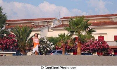 Brunette woman moves skipping towards sea coast