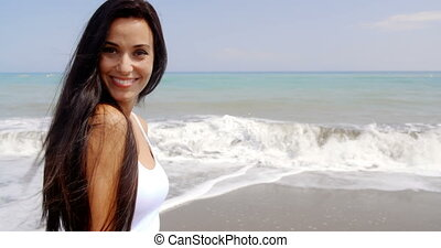 Brunette Woman on Beach Smiling Over Shoulder