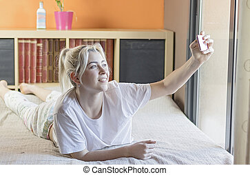 Brunette woman on her bed taking selfie on her phone