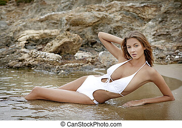 Brunette woman on the beach - Young fashion brunette woman...
