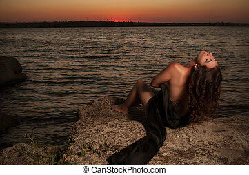 brunette woman on the sunset background covered with a black cloth