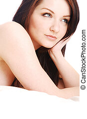 Brunette woman on white bed looking off to side