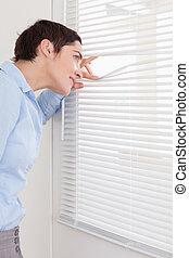 Brunette woman peeking out a window