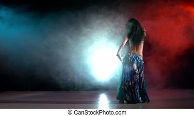 Brunette woman performing belly dance, on red, blue, smoke, slow motion