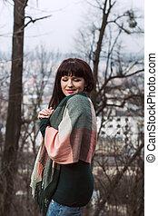 Brunette woman posing in a scarf