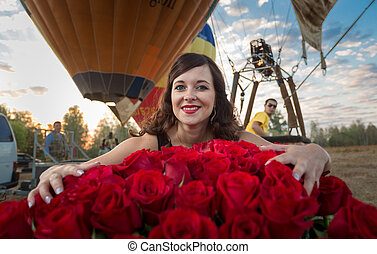 brunette woman posing with bouquet of roses against hot air balloons
