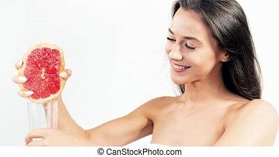 Brunette Woman Pressing Grapefruit Juice to Glass - Smiling...