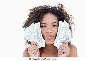 Brunette woman puckering her lips while holding two fans of bank notes